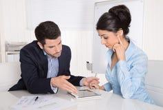 Succesvolle commerciële teamzitting bij bureau die tabletcompu bekijken Royalty-vrije Stock Foto