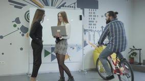 Succesvolle creatieve gebaarde werkgever in vrijetijdskleding die een fiets berijden rond het bureau Het hoofd verspreidt documen stock videobeelden
