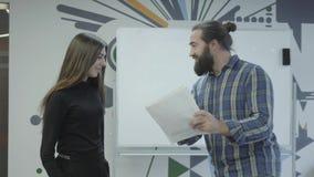 Succesvolle creatieve gebaarde werkgever in vrijetijdskleding die een vleetraad berijden rond het bureau De manager is tevreden m stock video