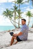 Succesvolle freelancerzakenman met laptop op het strand Stock Afbeelding