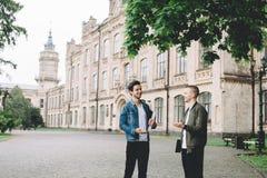 Succesvolle gelukkige studenten die dichtbij campus of universiteit zich buiten bevinden stock afbeelding