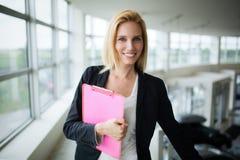 Succesvolle glimlachende bedrijfsvrouw bij de documenten van de het werkholding, die zich dichtbij venster in bureau bevinden royalty-vrije stock foto's
