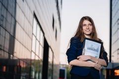 Succesvolle glimlachende zakenman, die zich tegen de achtergrond die van gebouwen bevinden omslag met verkoopgrafieken houden Sta Stock Foto's
