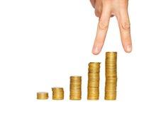 Succesvolle hand op de bovenkant van de stapel van het gouden muntstuk. Royalty-vrije Stock Afbeelding
