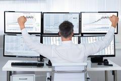 Succesvolle Handelaar With Arms Raised die Grafieken op de Schermen bekijken stock afbeeldingen