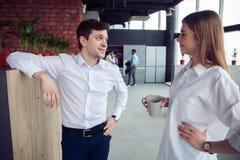Succesvolle jonge bedrijfsmensen die idee?n delen en tijdens de koffiepauze glimlachen stock foto's