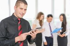 Succesvolle jonge de tabletpc van de bedrijfsmensenholding met zijn team Royalty-vrije Stock Foto