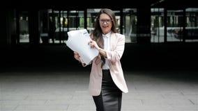 Succesvolle Jonge Kaukasische Bedrijfsvrouw die Haar Wapens met Documentomslag opheffen bij Stedelijke de Bouwachtergrond gelukki stock footage