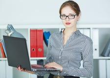 Succesvolle jonge laptop van de vrouwenholding in handen die in camera kijken Stock Afbeelding