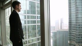 Succesvolle jonge zakenman die aan vloer-aan-plafond venster komen, die cityscape bekijken stock videobeelden