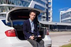 Succesvolle jonge zakenman die freelancer buiten in de stad werken de mens zit op autolaars met tablet stock foto