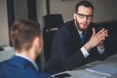 Succesvolle kleine bedrijfseigenaar die zich met gekruiste wapens met werknemer in het backgrounding van zeker zakenmanportret be Stock Fotografie