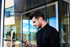 Succesvolle mannelijke financier die e-mail in Internet via cellphone controleren, die zich buiten bedrijf bevinden royalty-vrije stock foto's