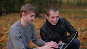 Succesvolle mens twee die laptop Internet en het typen met behulp van stock videobeelden