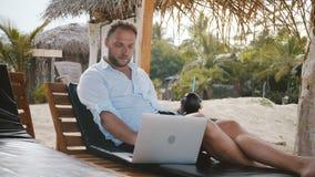 Succesvolle midden oude mannelijke freelance arbeider met fruitdrank het ontspannen als zitkamervoorzitter op de zomerstrand, die stock footage