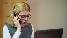 Succesvolle onderneemster die aan laptop in bureau werken, die op de telefoon spreken stock videobeelden