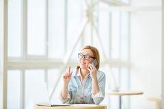 Succesvolle onderneemster die op telefoon spreken stock afbeelding