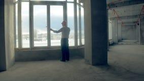 Succesvolle ondernemende jonge zakenman die op de telefoon dichtbij panoramisch venster in de nieuwe bouw, onvolledig bureau spre stock videobeelden