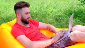 Succesvolle online transactie of het winnen van een computerspel De kerel in de rode T-shirt ligt op een opblaasbare matras die w stock footage
