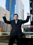Succesvolle opgewekte zakenman en het gelukkige doende teken van de wapenwinnaar Stock Fotografie