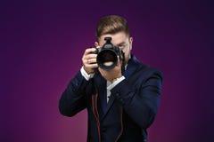Succesvolle professionele fotograaf in de digitale camera van het smokinggebruik DSLR op donkere achtergrond Royalty-vrije Stock Afbeelding