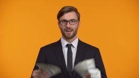 Succesvolle rijke man die bos van dollars en het knipogen gemakkelijk inkomen op Internet tonen stock footage