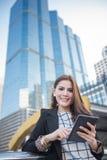 Succesvolle slimme bedrijfsvrouw die de computer van de zekere en het glimlachen holdingstablet kijken stock fotografie
