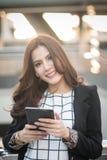Succesvolle slimme bedrijfsvrouw die de computer van de zekere en het glimlachen holdingstablet kijken stock foto's