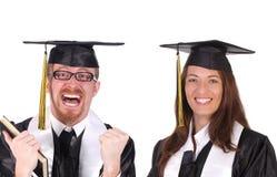 Succesvolle student twee in graduatietoga's Stock Foto's