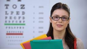 Succesvolle vrij vrouwelijke oftalmoloogstudent die in glazen aan camera glimlachen stock videobeelden