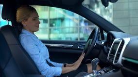 Succesvolle vrouw het strijken auto met liefde, aankoop van luxe auto, gelukkige koper stock fotografie