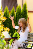 Succesvolle vrouw met laptop in de tuin Stock Fotografie