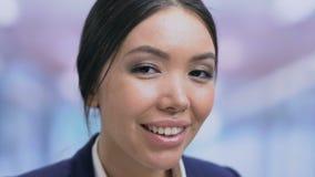Succesvolle vrouwelijke bureaumanager die en aan camera, gezichtsclose-up glimlachen kijken stock video