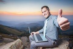 Succesvolle zakenman bovenop berg, die laptop met behulp van Royalty-vrije Stock Afbeelding