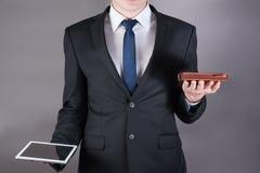 Succesvolle zakenman die een een tabletcomputer en agenda houden Grijze achtergrond Royalty-vrije Stock Afbeeldingen
