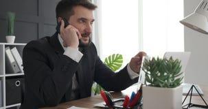 Succesvolle zakenman die laptop en mobiele telefoon met behulp van op kantoor stock videobeelden
