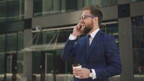 Succesvolle zakenman die met kop van koffie, hebbend telefoonbespreking met zijn partner buiten in de zaken lachen stock video