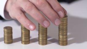 Succesvolle zakenman die muntstuk op stapel, investering zetten voortaan, close-up stock videobeelden