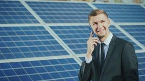 Succesvolle zakenman die op de telefoon op de achtergrond van een zonnekrachtcentrale spreken royalty-vrije stock foto's