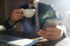 Succesvolle Zakenman Holding Smartphone in Zonlicht Stock Afbeelding
