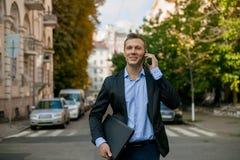 Succesvolle zakenman in kostuum met laptop in de stad royalty-vrije stock foto's