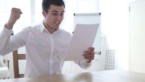 Succesvolle Zakenman Reading Documents en het Vieren Winst stock footage