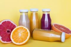 Succhi freschi di pompelmo e dell'arancia con i frutti, isolati su fondo giallo immagine stock