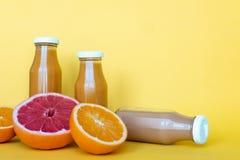 Succhi freschi di pompelmo e dell'arancia con i frutti, isolati su fondo giallo Posto per testo immagini stock libere da diritti