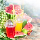 Succhi sani freschi luminosi, frutta, ananas, anguria sull'estate di legno del fondo, resto, fine sana di stile di vita Fotografie Stock Libere da Diritti