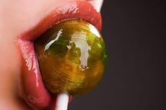 Succhiamento del lollipop Immagini Stock