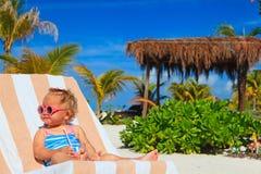 Succo bevente della bambina sveglia sulla spiaggia tropicale Fotografia Stock