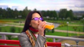 Succo d'arancia bevente della donna bella giovane all'aperto al parco di estate 4 K video d archivio