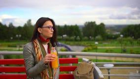 Succo d'arancia bevente della donna bella giovane all'aperto al parco di estate 4 K archivi video