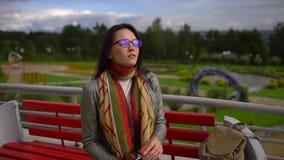 Succo d'arancia bevente della donna bella giovane all'aperto al parco di estate Rallentatore video d archivio